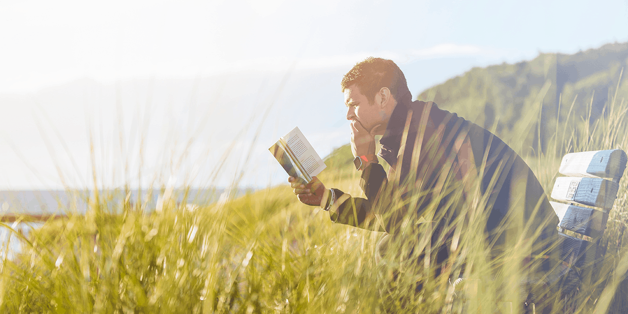 Man sitting on a bench in a field reading a book about investing