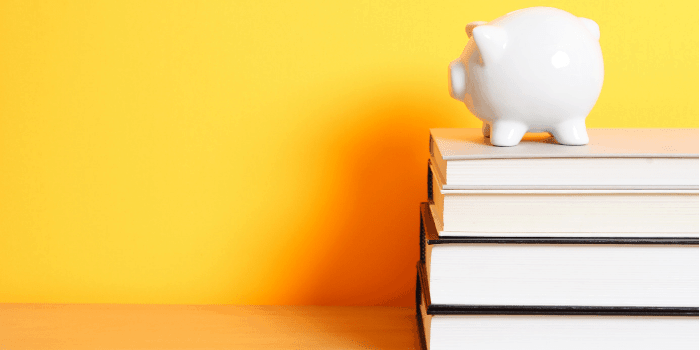 A piggy bank on top of a stack of books with yellow background