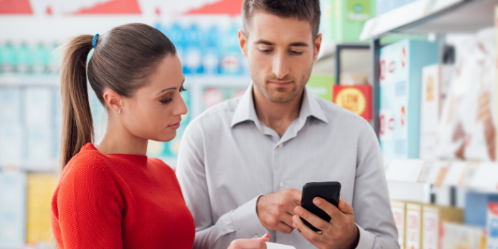 couple budgeting with app in grocery store