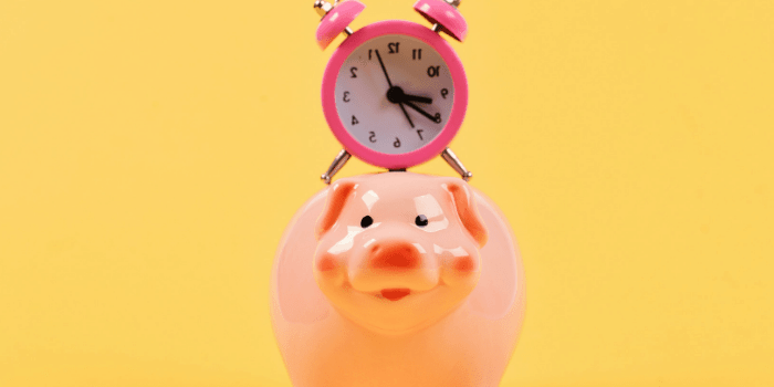 piggy bank with clock on top yellow background