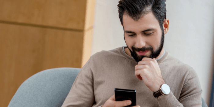 man sitting in armchair and looking at smartphone