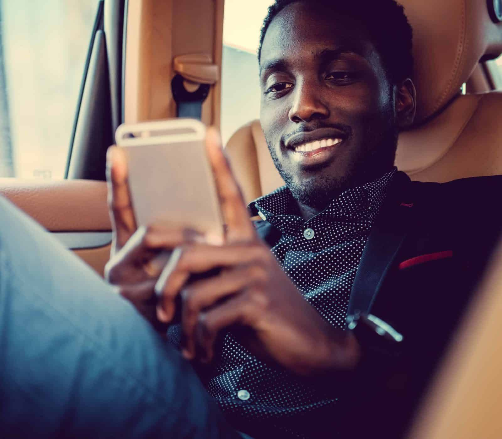 Well dressed smiling African American man using a smartphone in a car.