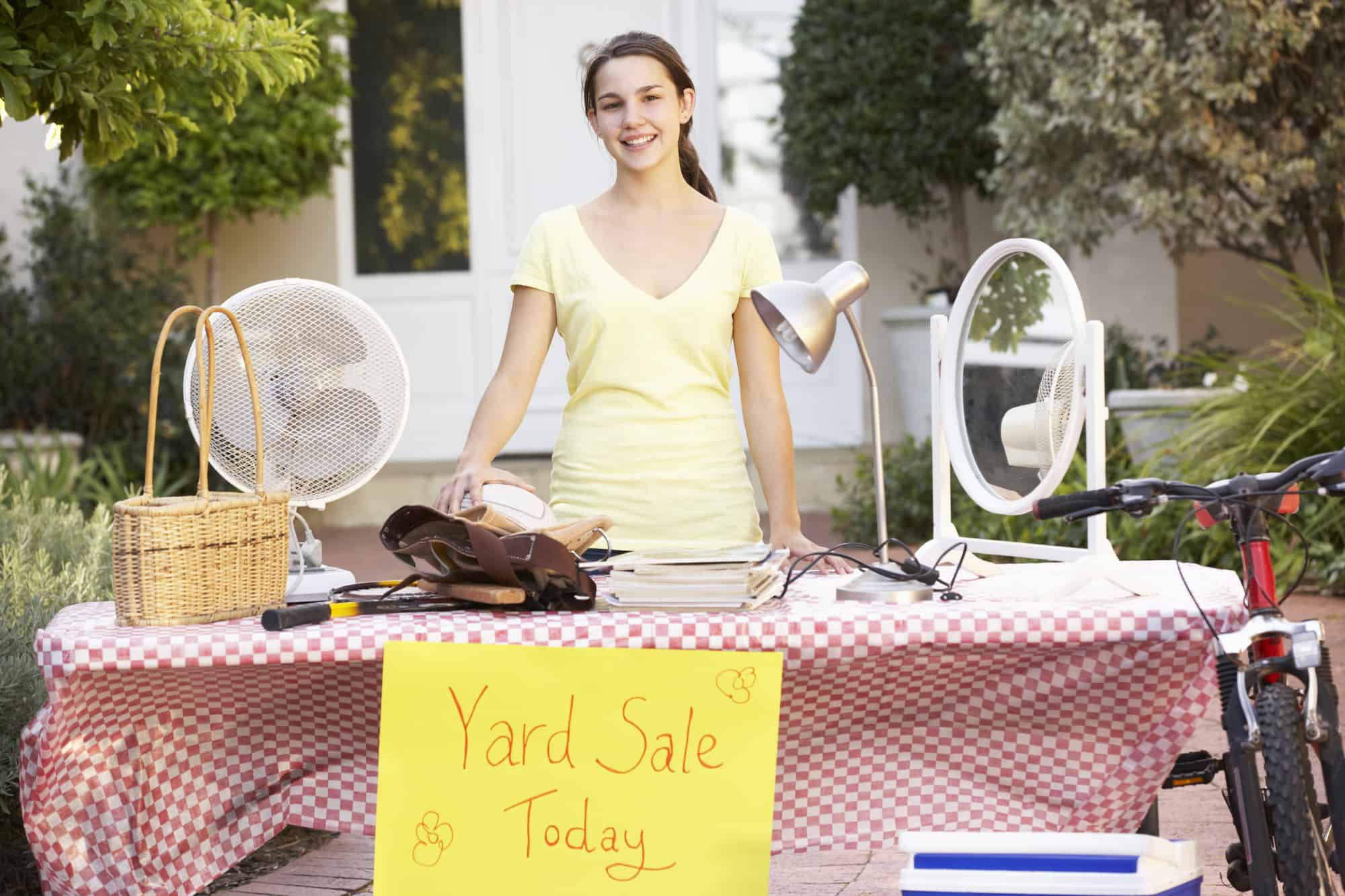 Teenage Girl Holding Yard Sale