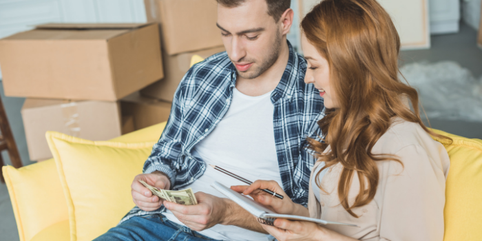 Couple sitting on the couch counting cash with boxes in background