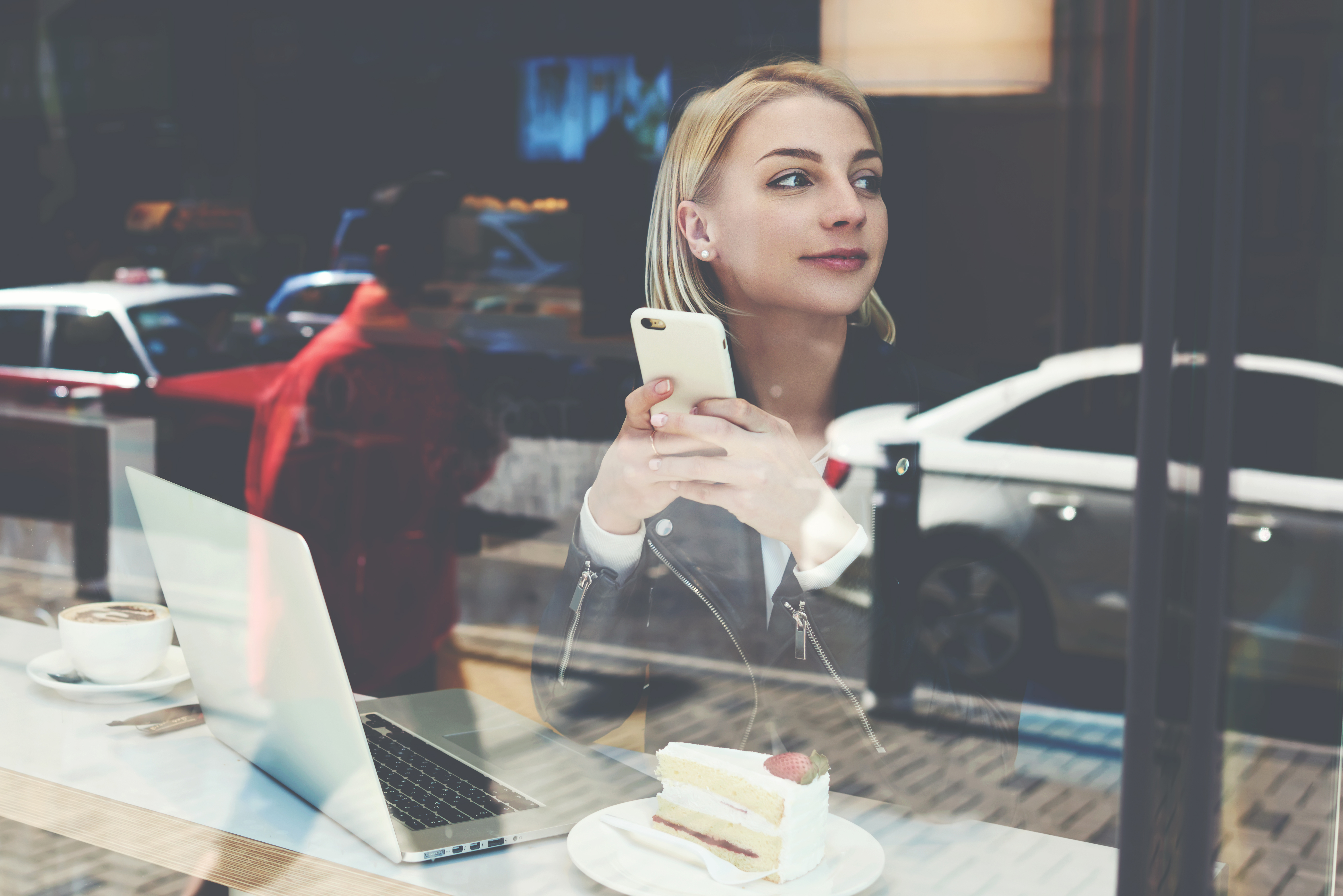 A young blonde woman is working on a laptop at a cafe. She holds her phone in hand and gazes off to the side, contemplating something with a content look on her face.