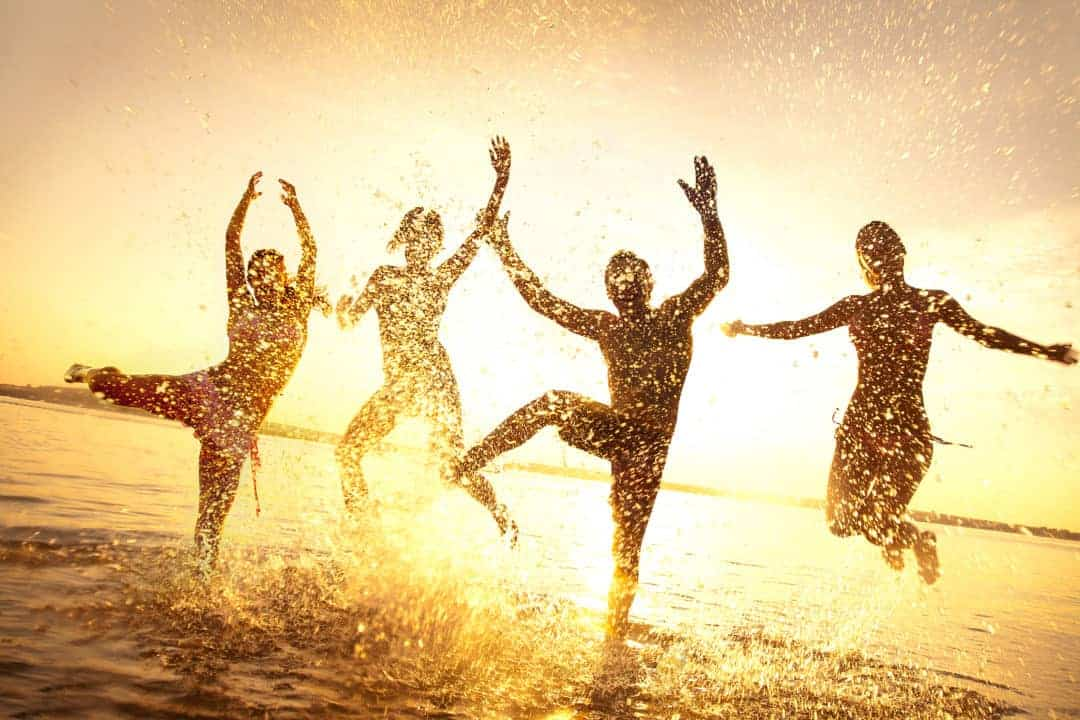 group of happy young people dancing and splashing at the beach on beautiful summer sunset