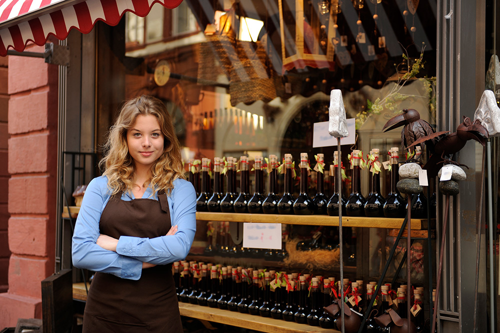 A woman business owner stands in front of her wine shop