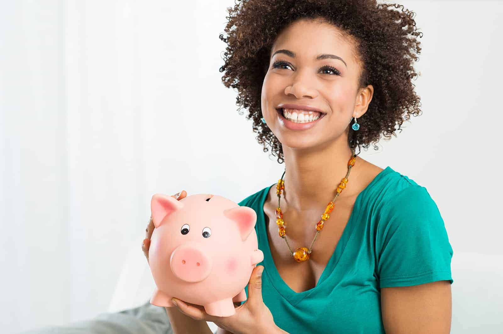 Happy Young Woman Saves Money in Piggy bank