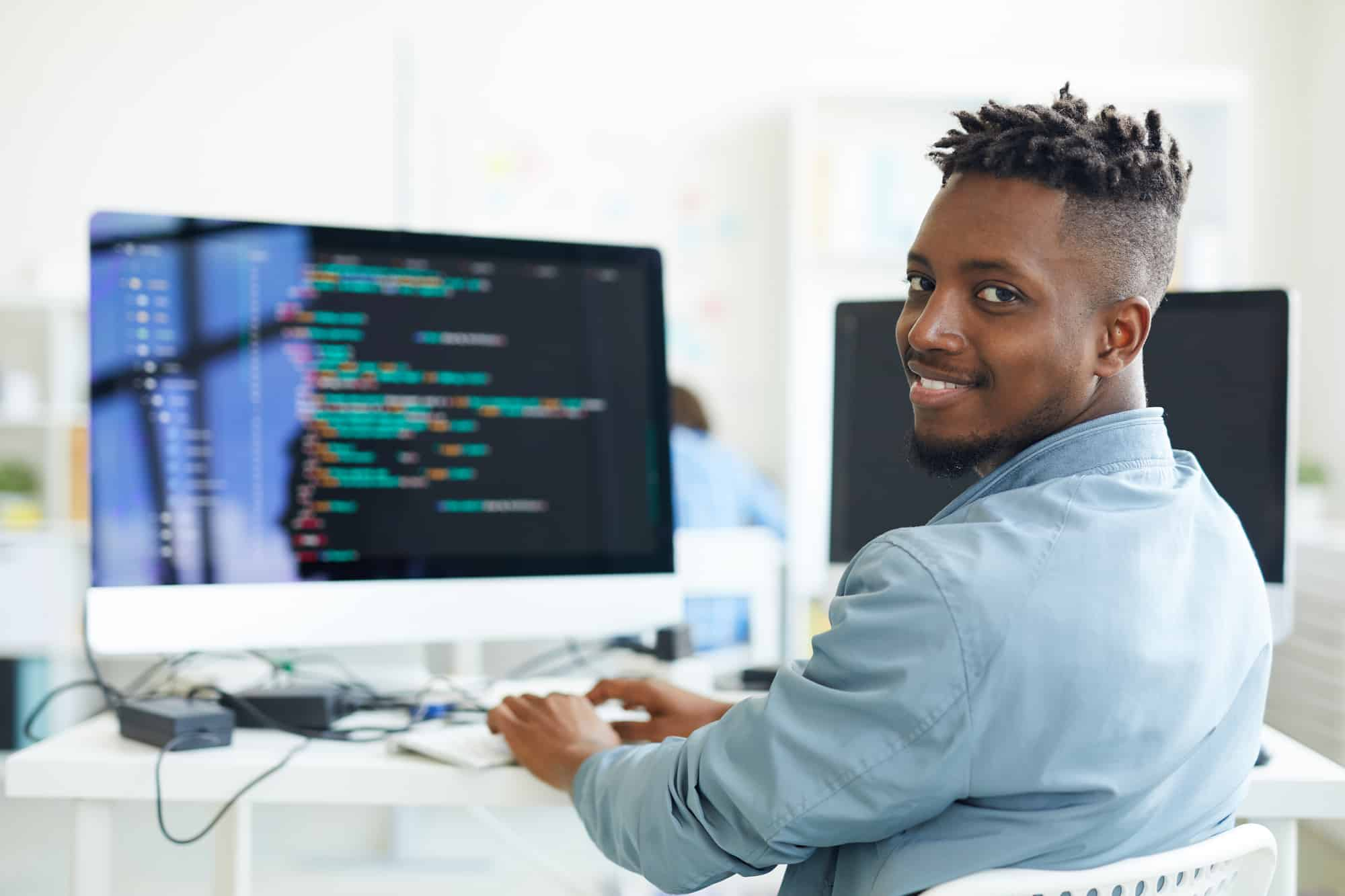 A young man works on an iMac, coding