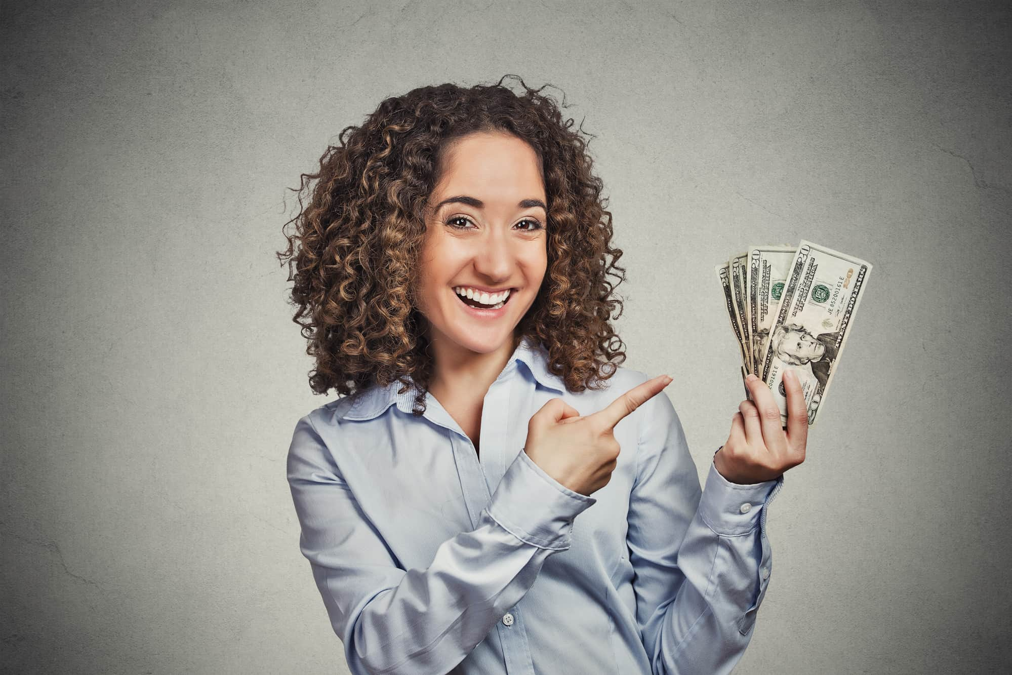 A happy woman holding money