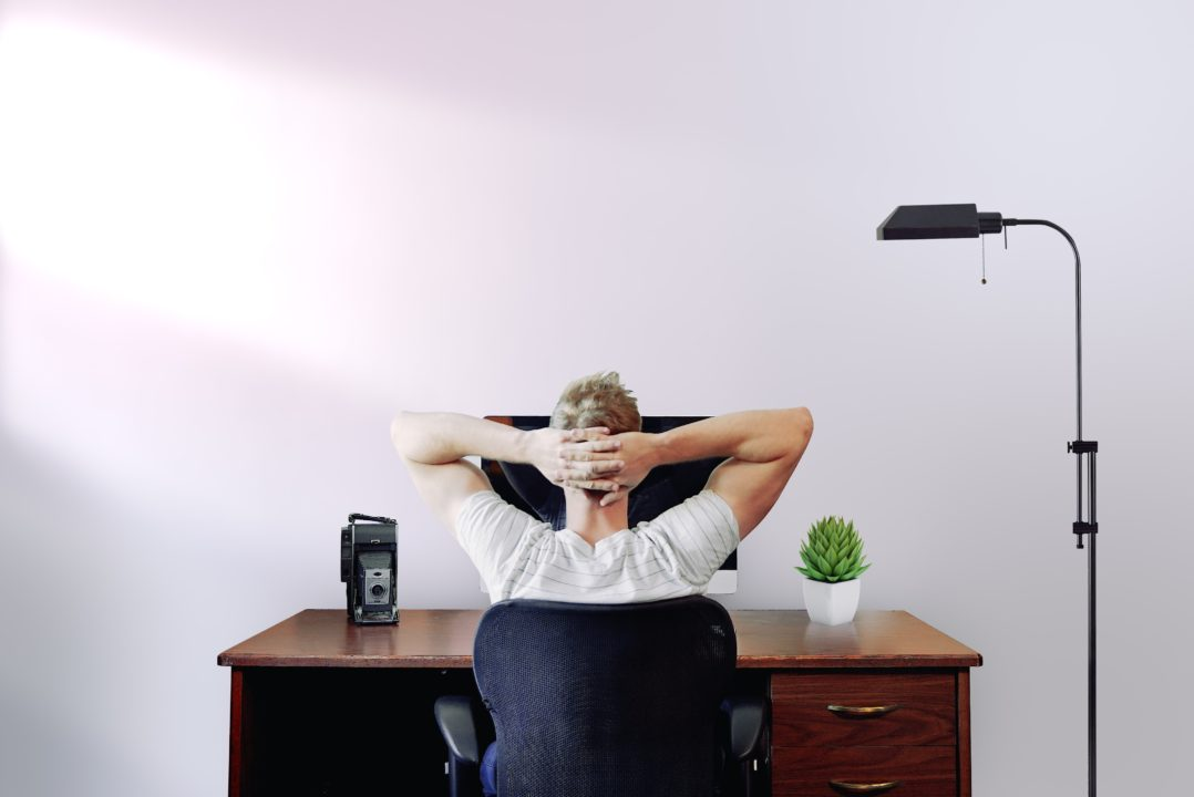 Man sits at desk with arms behind head