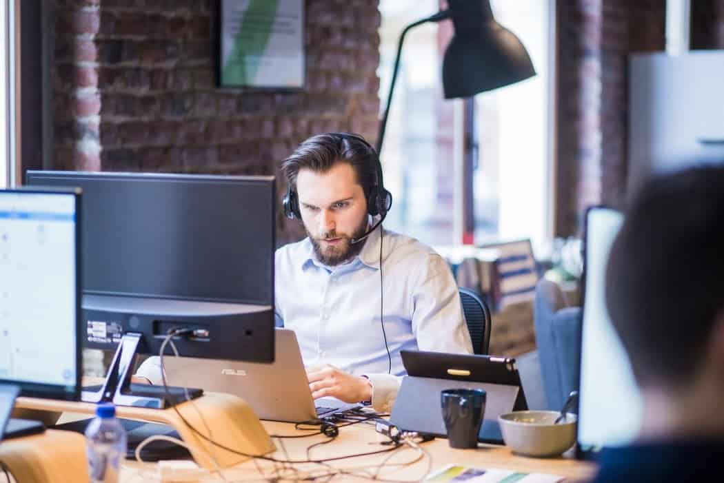 Man on laptop with headset on